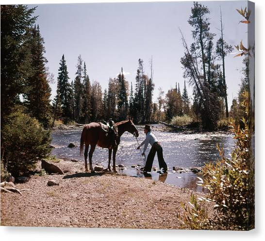 Lead Character Canvas Print - 1970s Cowboy Standing In Stream Leading by Vintage Images