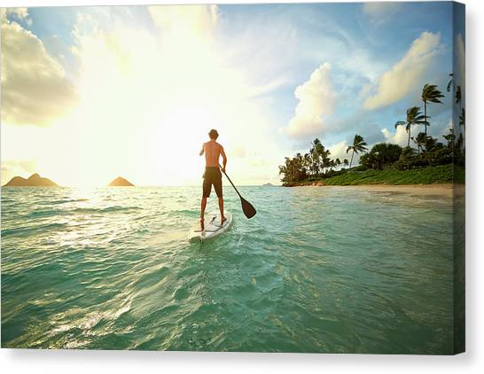 Caucasian Man On Paddle Board In Ocean Canvas Print by Colin Anderson Productions Pty Ltd