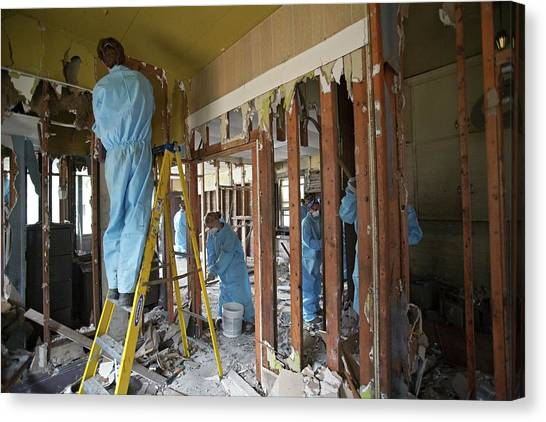 Protective Clothing Canvas Print - Repairing Flood Damage by Jim West