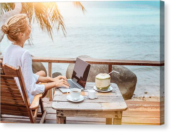 Young Woman Working On Laptop With Coffee And Young Coconut Canvas Print by Jasmina007