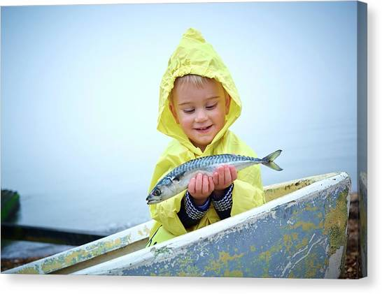 Raincoat Canvas Print - Boy Wearing Raincoat Holding A Mackerel by Ruth Jenkinson