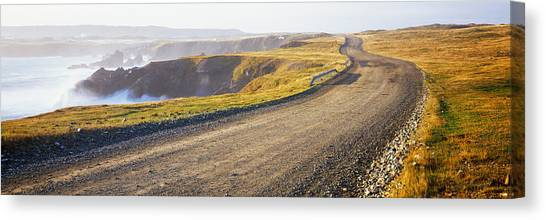 Newfoundland And Labrador Canvas Print - Dirt Road Passing Through A Landscape by Panoramic Images