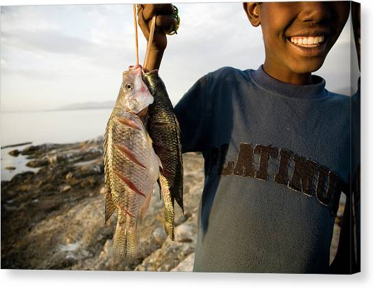 Local Food Canvas Print - A Boy Smiles While Holding A String by Michael Hanson