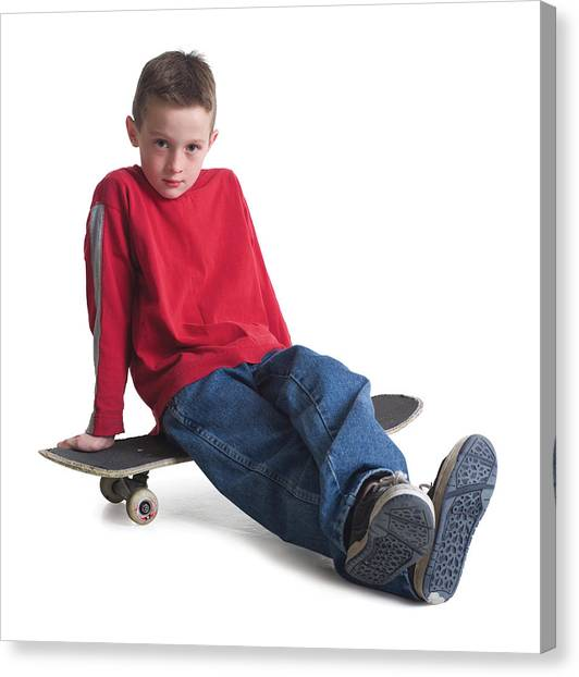 A Caucasian Boy In Jeans And A Red Sweater Sits On His Skateboard And Smiles Slightly Canvas Print by Photodisc