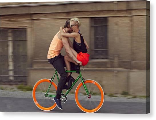 A Couple Biking Through The City Canvas Print by Justin Case
