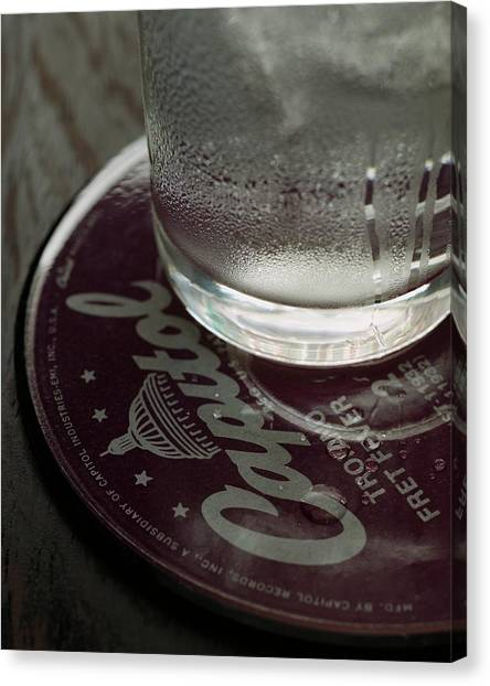 A Glass On A Coaster Canvas Print by Romulo Yanes