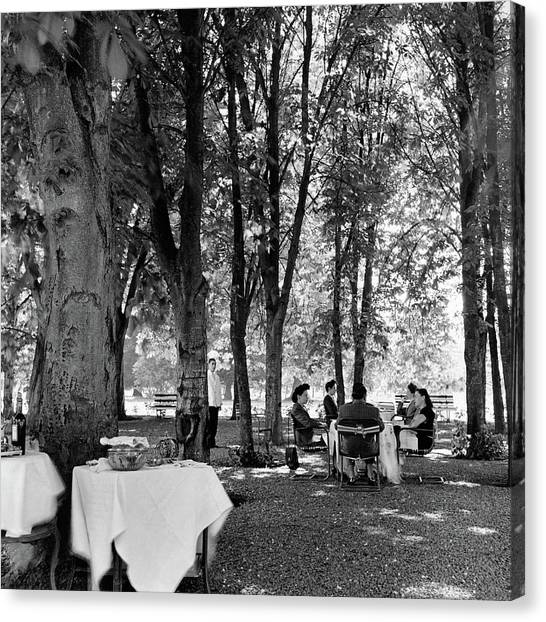 A Group Of People Eating Lunch Under Trees Canvas Print