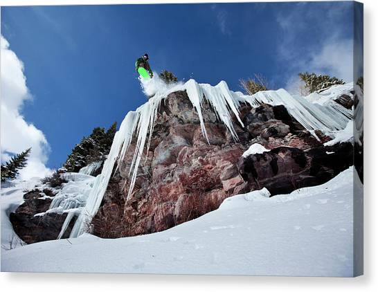 Stalactites Canvas Print - A Male Snowboarder Jumps Off An Ice by Patrick Orton