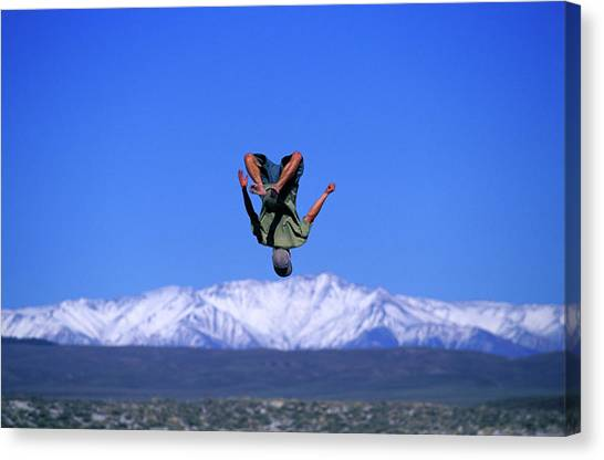 Trampoline Canvas Print - A Man Does A Backflip On A Trampoline by Corey Rich