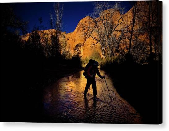 Backpacks Canvas Print - A Man Hikes Through A Stream As The Sun by Kirk Mastin