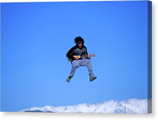 Trampoline Canvas Print - A Man Plays The Guitar While Jumping by Corey Rich