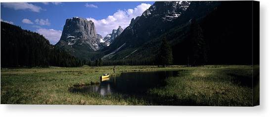 Teton National Forest Canvas Print - A Man Pulls His Canoe Up A River by David Stubbs