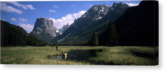 Teton National Forest Canvas Print - A Man Pulls His Canoe Up A River Valley by David Stubbs