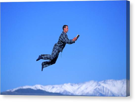 Trampoline Canvas Print - A Man Reads A Book While Jumping by Corey Rich