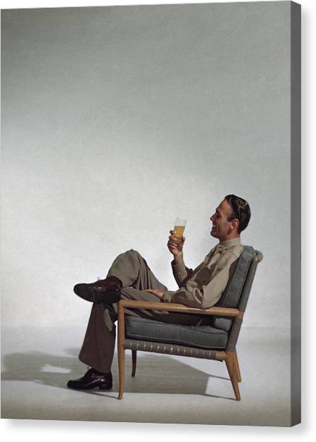 A Man Sitting In An Armchair With A Drink Canvas Print