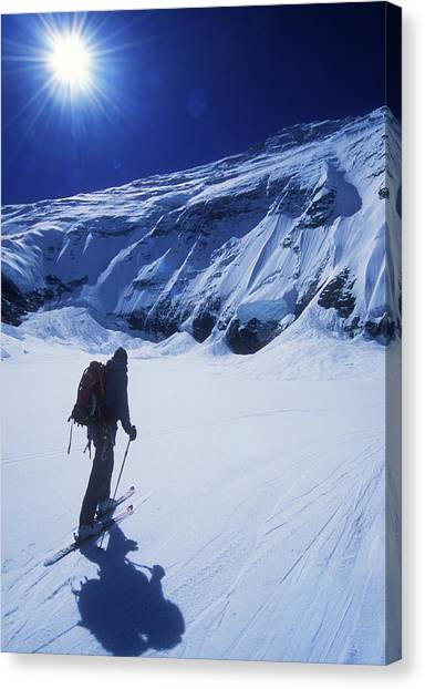 Mount Everest Canvas Print - A Man Ski Touring Under Blue Skies by Jimmy Chin