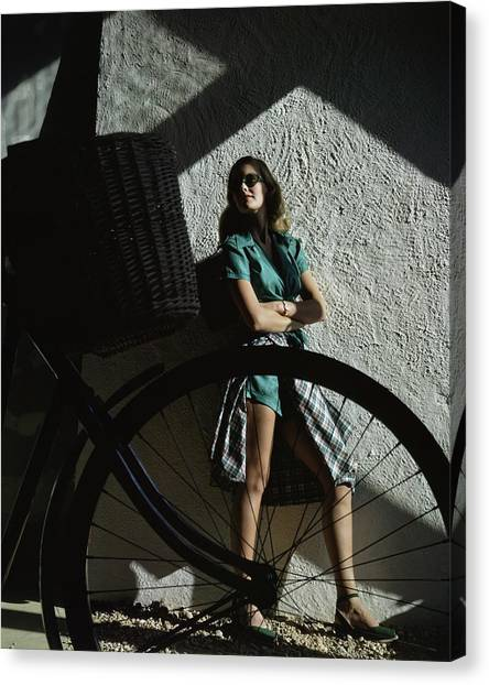 A Model Behind A Bicycle Canvas Print by John Rawlings