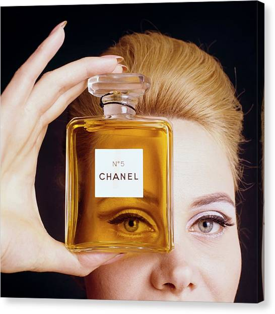 Chanel Canvas Print - A Model Holding A Bottle Of Perfume by Fotiades