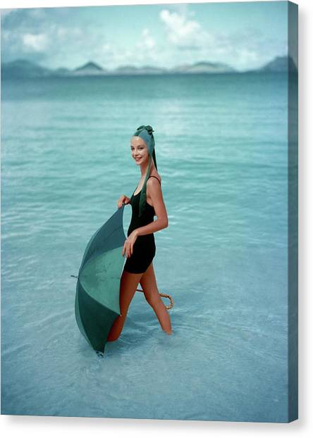 A Model In The Sea With An Umbrella Canvas Print by Richard Rutledge