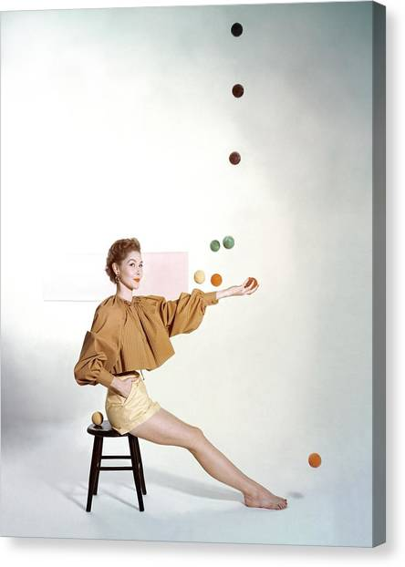 A Model Sitting On A Stool Juggling Canvas Print
