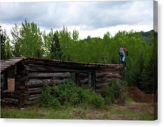 Log Cabin Canvas Print - A Mountain Biker Jumps Off A Log Cabin by Patrick Orton