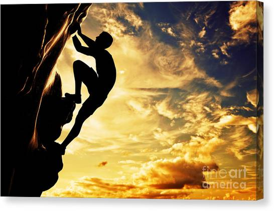 A Silhouette Of Man Free Climbing On Rock Mountain At Sunset Canvas Print