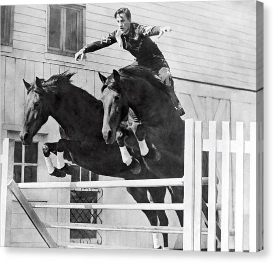 Bareback Canvas Print - A Stunt Rider On Two Horses. by Underwood Archives