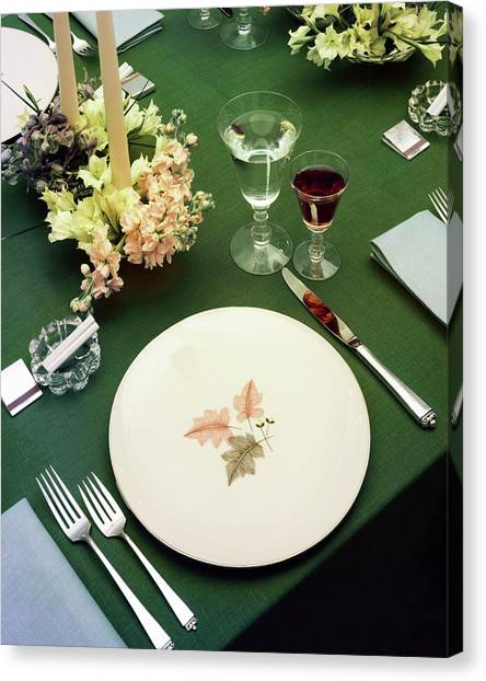 A Table Setting On A Green Tablecloth Canvas Print