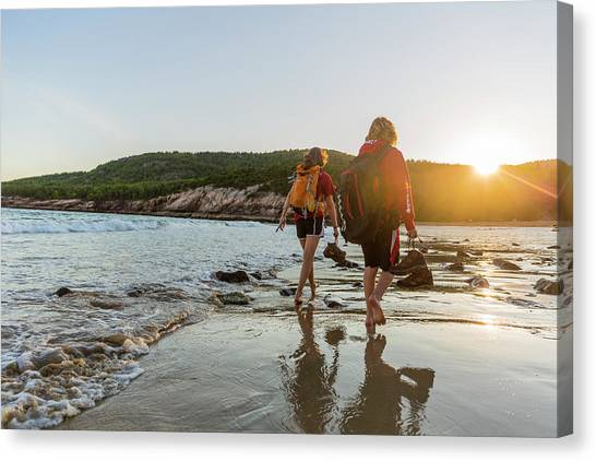 People Walking On Beach Canvas Print - A Teenage Boy And Girl Walk On Sand by Jerry Monkman
