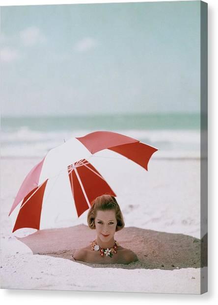 A Woman Buried In Sand At A Beach Canvas Print by Richard Rutledge
