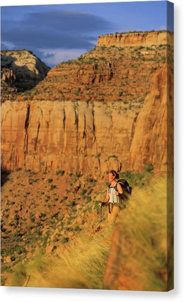 Backpacks Canvas Print - A Woman Hikes Along The Base Of A Wall by Rich Wheater