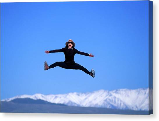 Trampoline Canvas Print - A Woman Spreads Her Arms And Legs Wide by Corey Rich