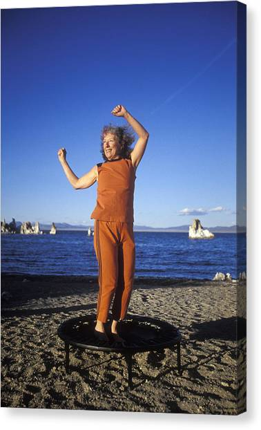 Trampoline Canvas Print - A Women In A Bright Orange Outfit Doing by Aaron Black
