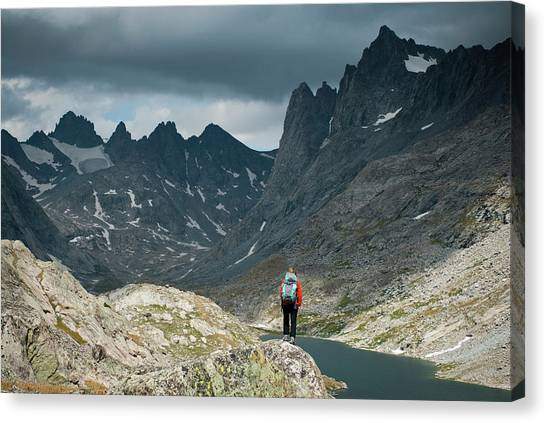 Backpacks Canvas Print - A Young Woman Takes In The View While by Jeff Diener