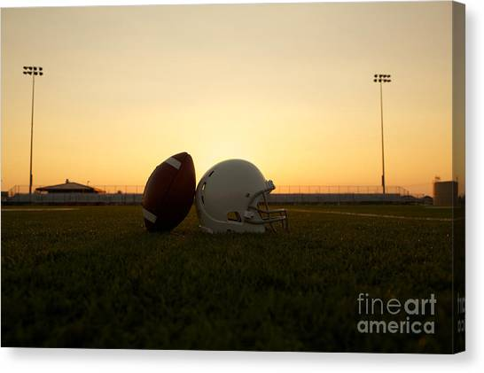 American Football And Helmet On The Field At Sunset Canvas Print