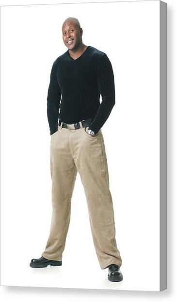 An African American Man In Tan Pants And A Black Shirt Puts His Hands In His Pockets And Smiles Canvas Print by Photodisc