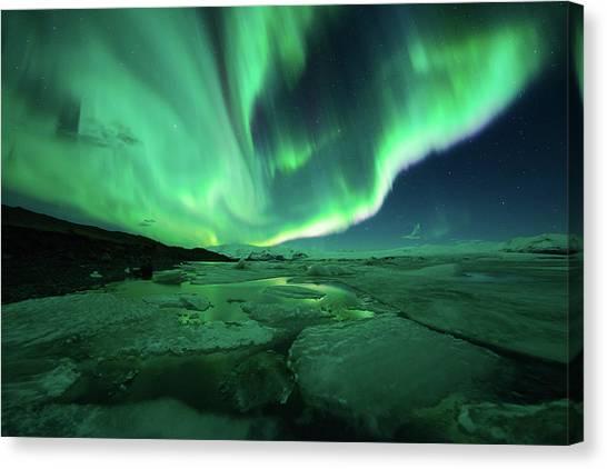 Aurora Display Over The Glacier Lagoon Canvas Print by Natthawat