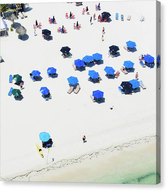 Blue Umbrellas On A Sunny Beach Canvas Print by Tommy Clarke