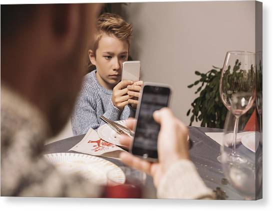 Boy Playing With His Smartphone After Christmas Dinner Canvas Print by Westend61