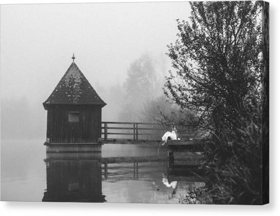 Bride In Foggy Landscape Sitting On A Jetty At A Lake Canvas Print by Leander Nardin