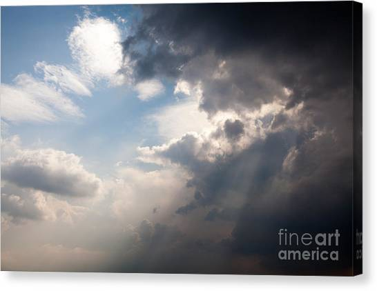 Broken Rain Clouds With Blue Sky And Sun Streaming Through Cloud Canvas Print