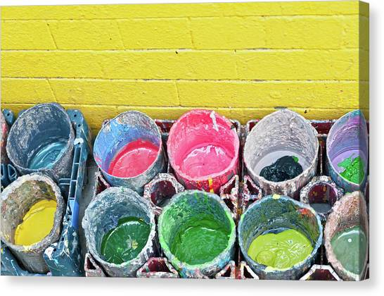 Buckets Of Colored Paints And A Yellow Canvas Print