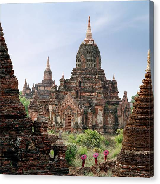 Buddhist Monks Walking Past Temple Canvas Print by Martin Puddy