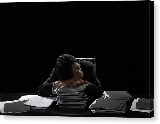 Businessman Asleep At Desk Resting Head On Stack Of Files Canvas Print by James Woodson