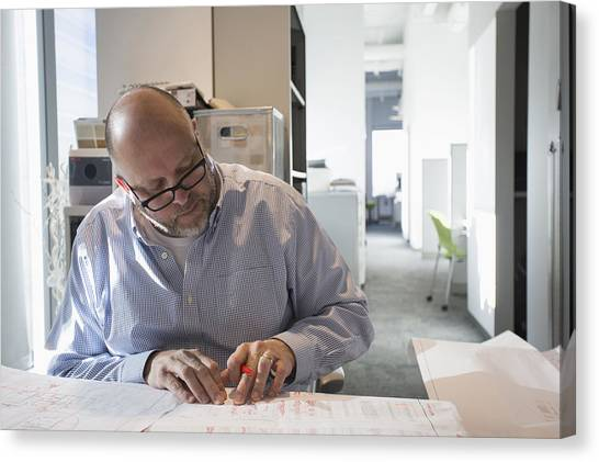 Businessman Sketching Blueprints In Office Canvas Print by Hill Street Studios