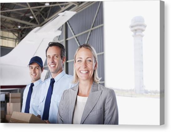 Businesswoman And Workers Standing In Hangar Canvas Print by Martin Barraud