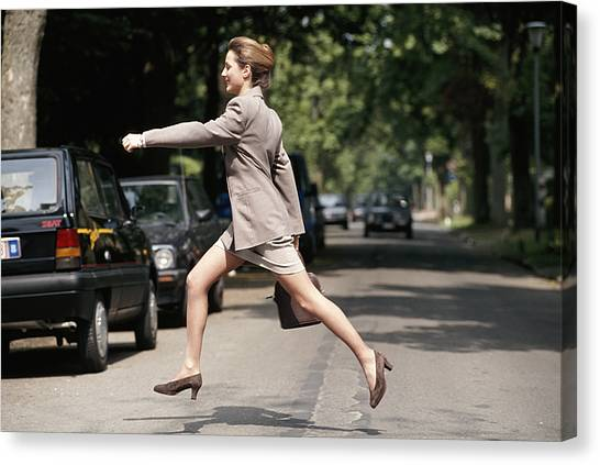 Businesswoman Running Across Road, Side View Canvas Print by David De Lossy