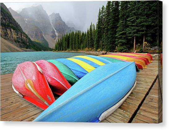 Canoes Line Dock At Moraine Lake, Banff Canvas Print by Wildroze