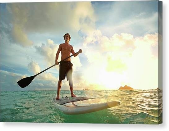 Caucasian Man On Paddle Board In Water Canvas Print by Colin Anderson Productions Pty Ltd