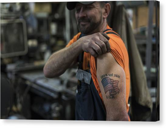 Caucasian Worker Displaying Tattoo In Factory Canvas Print by Jetta Productions Inc